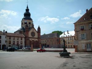 Senones - Square with a fountain, houses, church and an ancient abbey, clouds in the sky