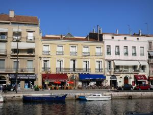 Sète - Houses, cafe terraces, boats moored to the quay, canal
