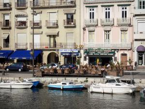 Sète - Buildings, cafe terraces, boats moored to the quay, canal