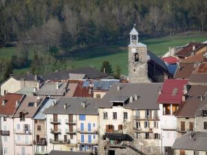 Seyne - Bell tower of the Pénitent chapel, houses of the old town, prairies and trees