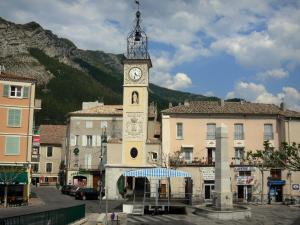 Sisteron - Clock tower topped by a forged iron campanile (bell tower), houses of the old town and fountain of the Docteur Robert square