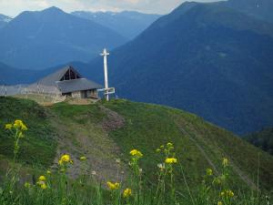 Superbagnères - Flora and wild flowers in foreground, contemporary-style chapel of the ski resort and the Pyrenees mountains