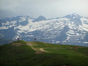 Superbagnères - Ski lifts of the ski resort, meadows and the Pyrenees mountains with some snow