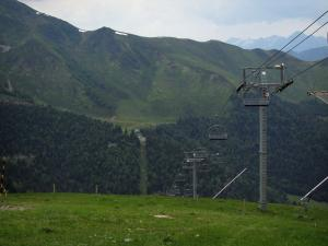 Superbagnères - Chairlift (ski lift) of the ski resort, meadow, forest and the Pyrenees mountains