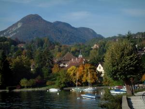 Talloires - Lake, port with boats, houses and church bell tower in the village, trees with autumn colours, forest and mountain
