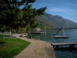 Talloires - Rivet, lake with pontoons, aquatic slide and buoys, mountain in background