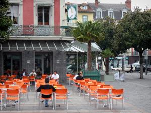 Tarbes - Verdun square : café terrace, potted palms, trees and buildings of the town