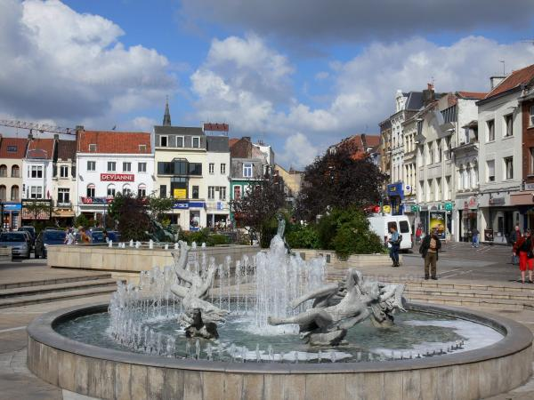 Tourcoing - Fountains of the Grand'Place square, shops and houses of the city, clouds in the blue sky
