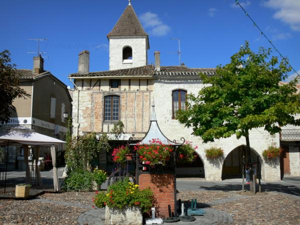 Tournon-d'Agenais - Bastide town: flower-bedecked well and houses of the Place des Cornières square, tower overlooking the place