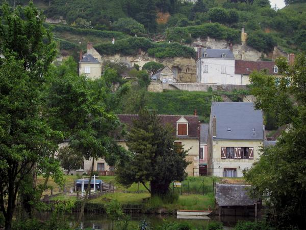 Trôo - Houses of the troglodyte village dominating the Loir River and trees along the water