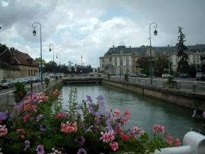Troyes - Rail of a bridge decorated with flowers and with a view of the river, lampposts and buildings of the city