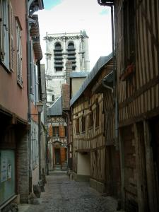 Troyes - Narrow paved street lined with old timber-framed houses, view of the tower of the Sainte-Madeleine church