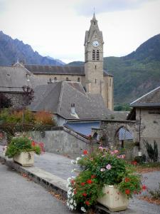 Valbonnais - Village in the Valbonnais area: church bell tower, roofs of houses and flowers, mountains in the background