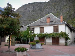 Valbonnais - Village of Entraigues: square with fountain, trees and flowers, houses of the village and mountains in the background