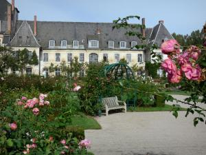 Valloires gardens - Rose in foreground, rose garden (rosebushes), bench and Valloires Cistercian abbey