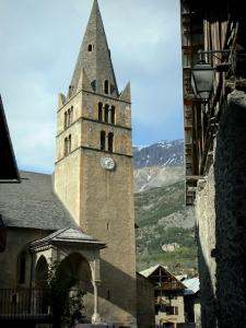 Vallouise - Bell tower and hall of the Saint-Etienne church, traditional chalets and mountain; in the Écrins National Nature Park