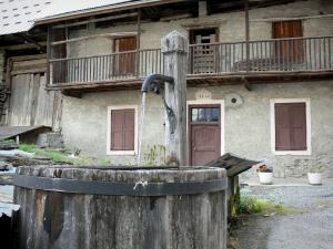 Vallouise - Wooden fountain and house of the village; in the Écrins National Nature Park