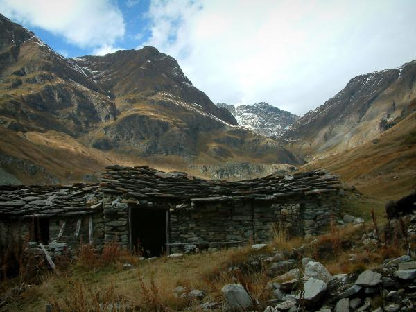 Vanoise massif - Vanoise national park: stone sheepfold (construction) with a slate roof, alpine lawns and mountains with snowy summits (Grande Alpes (Alps) road)