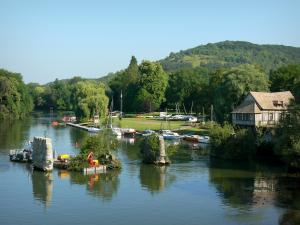 Vernon - River Seine, piles of the old medieval bridge, old half-timbered mill, boats and trees along the water