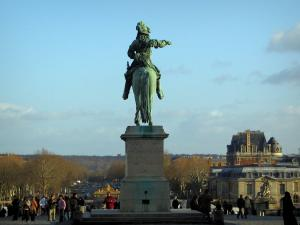 Versailles - Statue of Louis XIV with view of the entrance gate of the Palace of Versailles and the Paris avenue