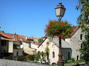 Verteuil-sur-Charente - Lamppost decorated with flowers, water mill and houses of the village; in the Charente valley