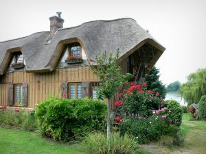 Vieux-Port - Half-timbered thatched cottage and its flower garden, the river Seine in the background; in the Norman Seine River Meanders Regional Nature Park, on the Thatched Cottage Route
