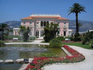 Villa Ephrussi de Rothschild - French-style formal garden (ornamental lake, fountains, flowers, paths, lawns, shrubs and palm trees) and facade of the Italian-style palace; in Saint-Jean-Cap-Ferrat
