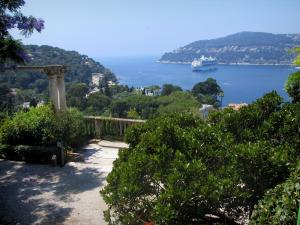 Villa Ephrussi de Rothschild - Garden of the palace with view of the natural harbour of Villefranche-sur-Mer, Mediterranean Sea with a cruise boat and the mount Boron in background
