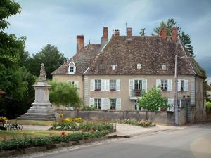 Villages of the Haute-Saône - Square with a statue and flowers, a road and a residence
