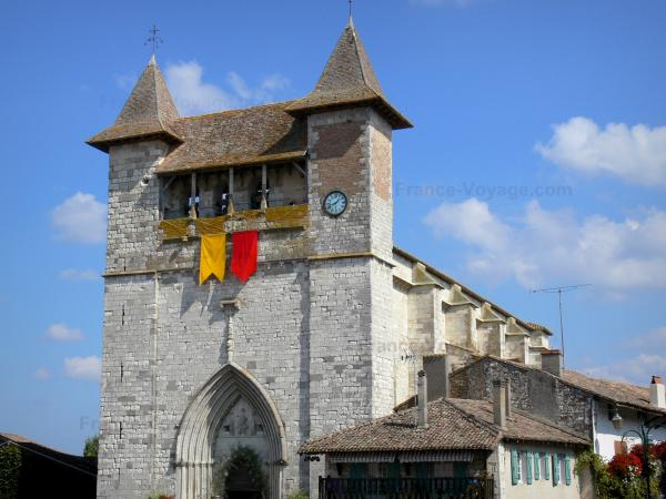 Villeréal - Medieval bastide town: fortified Notre-Dame church; clouds in blue sky