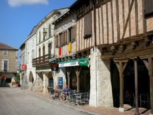Villeréal - Medieval bastide town: café terrace, houses and arcades of the Place de la Halle square