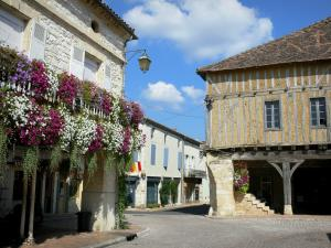 Villeréal - Medieval bastide town: flower-bedecked houses and arcades of the Place de la Halle square; clouds in blue sky