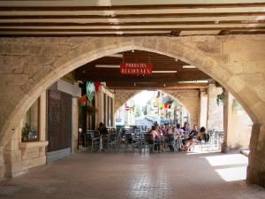 Villeréal - Medieval bastide town: café terrace under the arcades of the Place de la Halle square