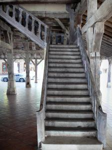 Villeréal - Medieval bastide town: staircase, pillars and wooden structure of the covered market hall