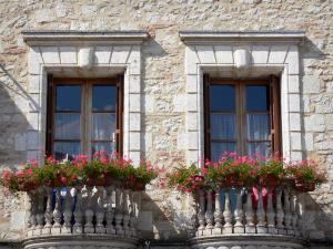 Villeréal - Medieval bastide town: facade of a stone house with its windows and flower-bedecked balconies