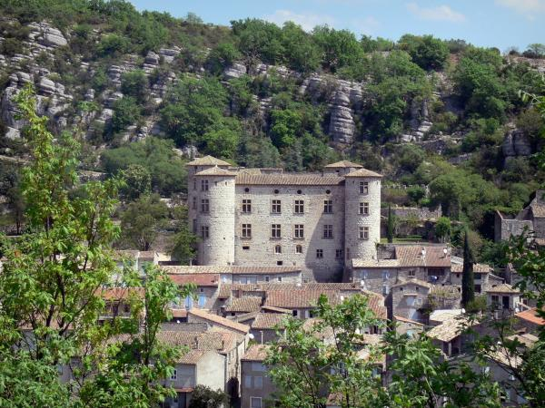 Vogüé - View of the castle and the roofs of the village of Vogüé at the foot of limestone cliffs