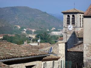 Vogüé - Bell tower of the Sainte-Marie church and houses of the village with a view of the surrounding hills